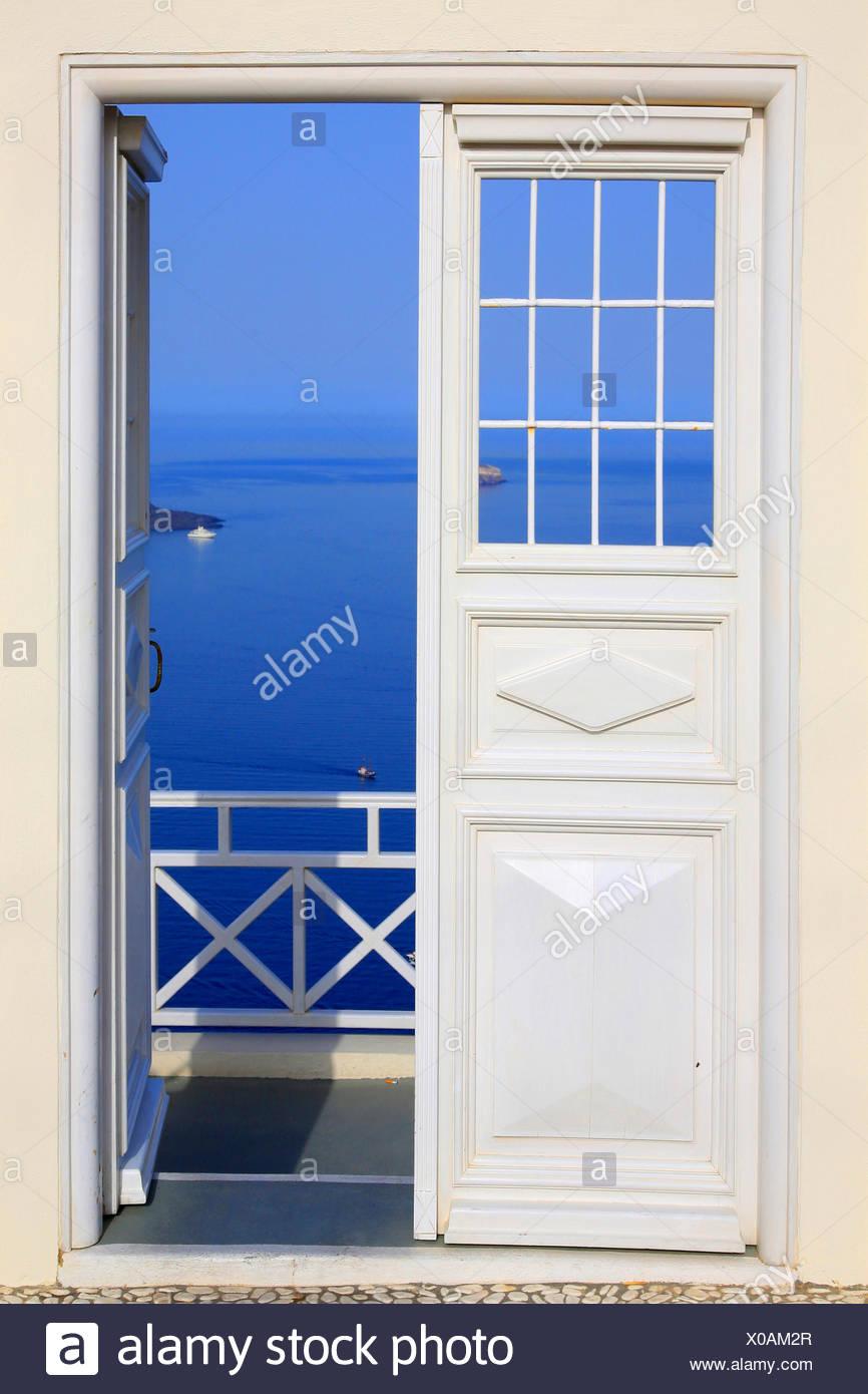 view through white door to the Mediterranean Sea, Greece, Cyclades, Santorin, Oia - Stock Image
