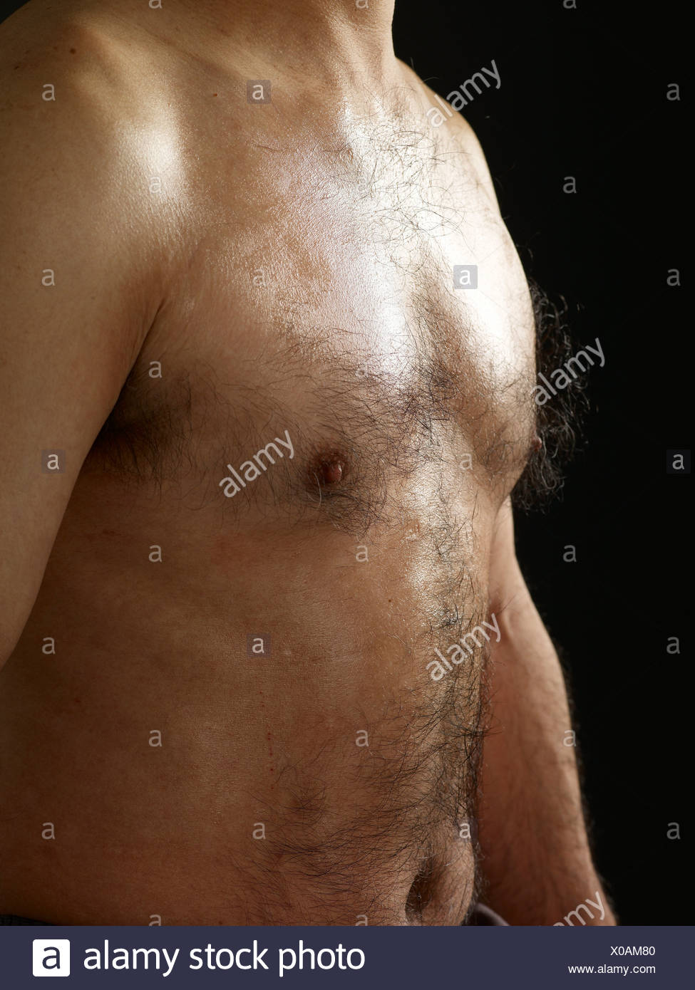Shirtless man with hairy chest side view - Stock Image