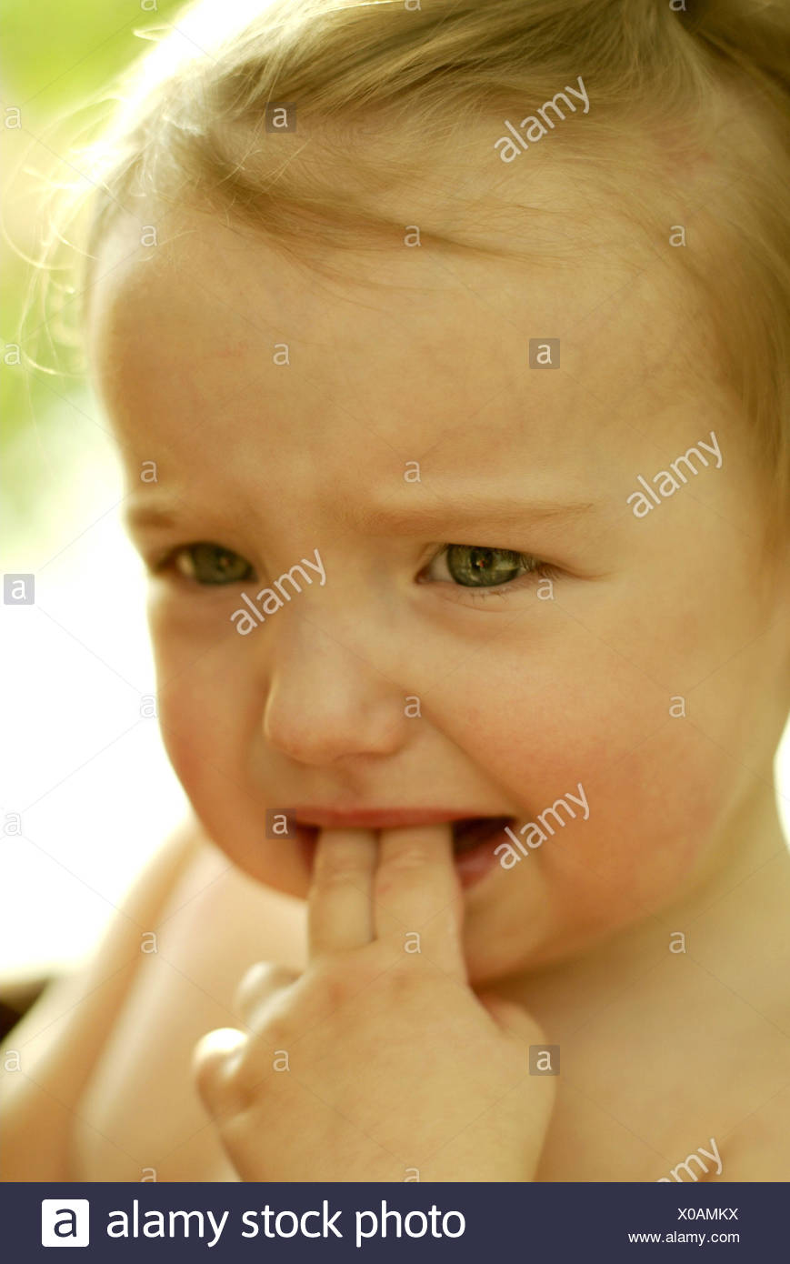 Girls, fingers, mouth, tearful, portrait, curled child portrait, child, 1 - 3 years, infant, blond, expression, unhappily, dissatisfied, discontent, tensely, cry, uncertainly, insecurity - Stock Image