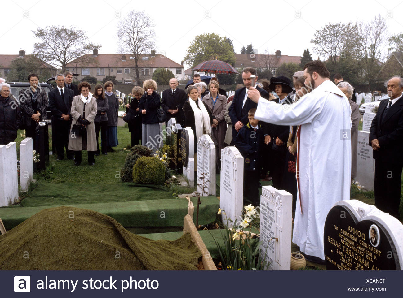 Catholic funeral where priest is blessing the coffin before it is covered with soil - Stock Image