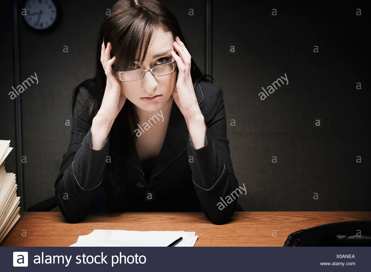 Stressed businesswoman at desk - Stock Image
