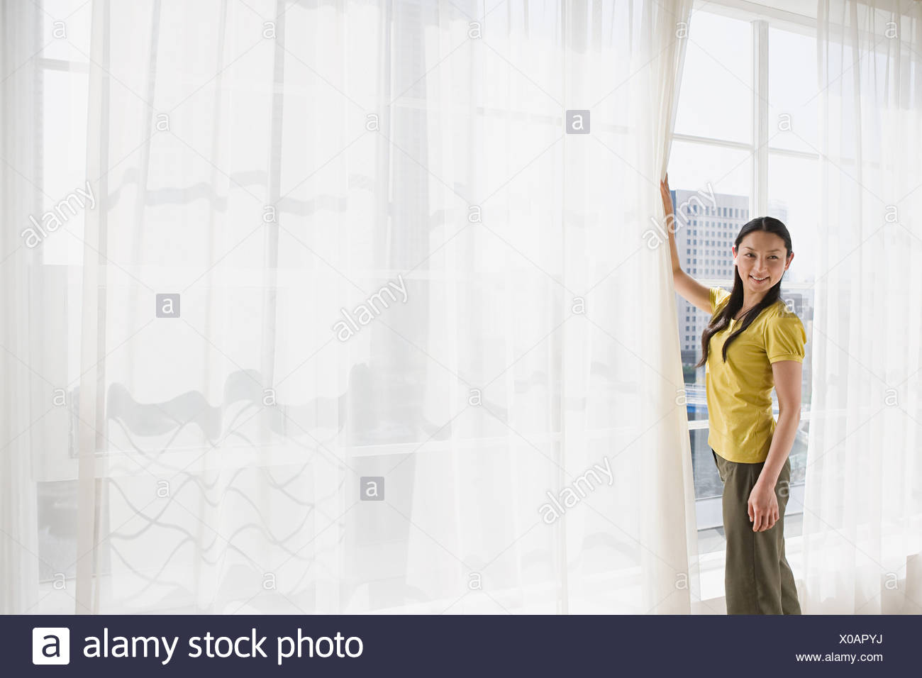 Japanese woman opening net curtains - Stock Image
