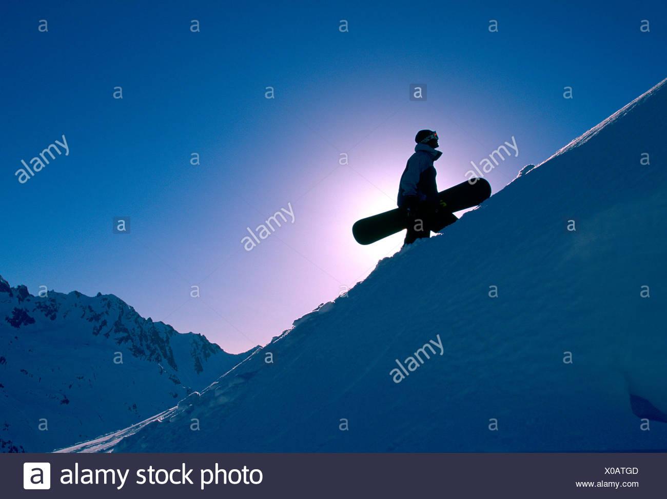Backlit snowboarder hiking uphill, Chamonix, France - Stock Image
