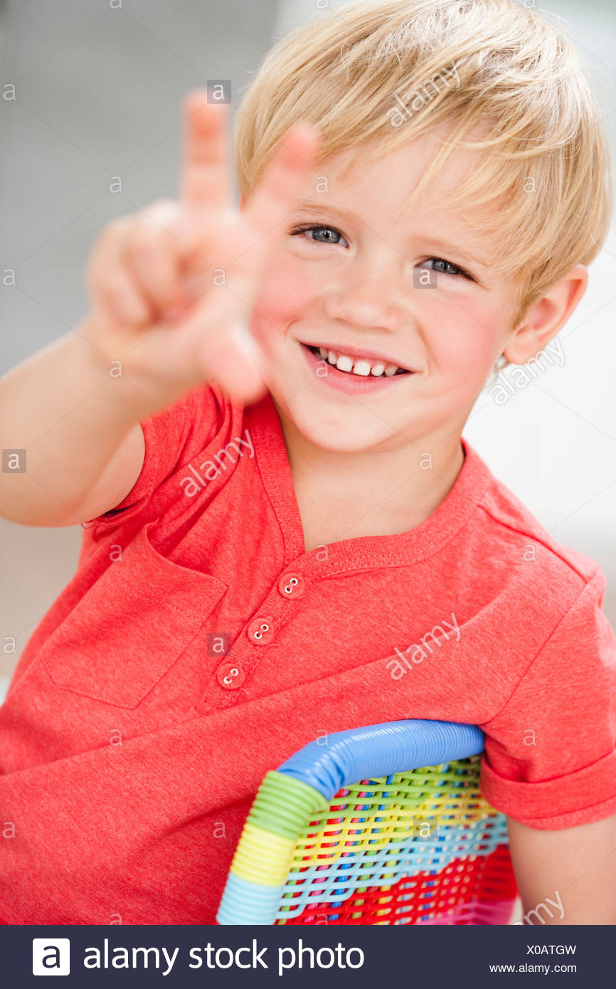 young boy holding up three fingers - Stock Image