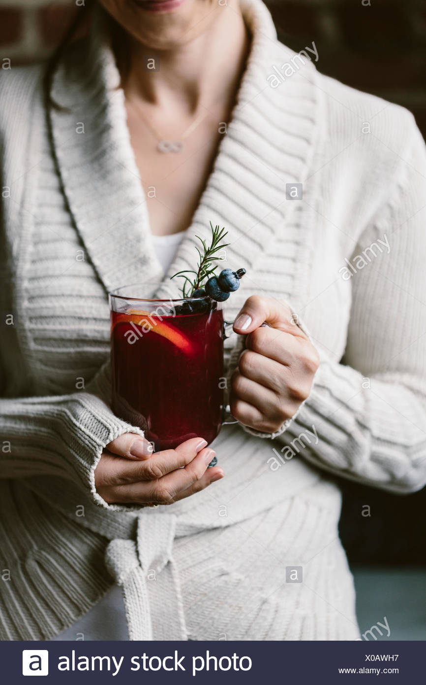 A woman is photographed with a glass of blueberry hot toddy in her hand Stock Photo