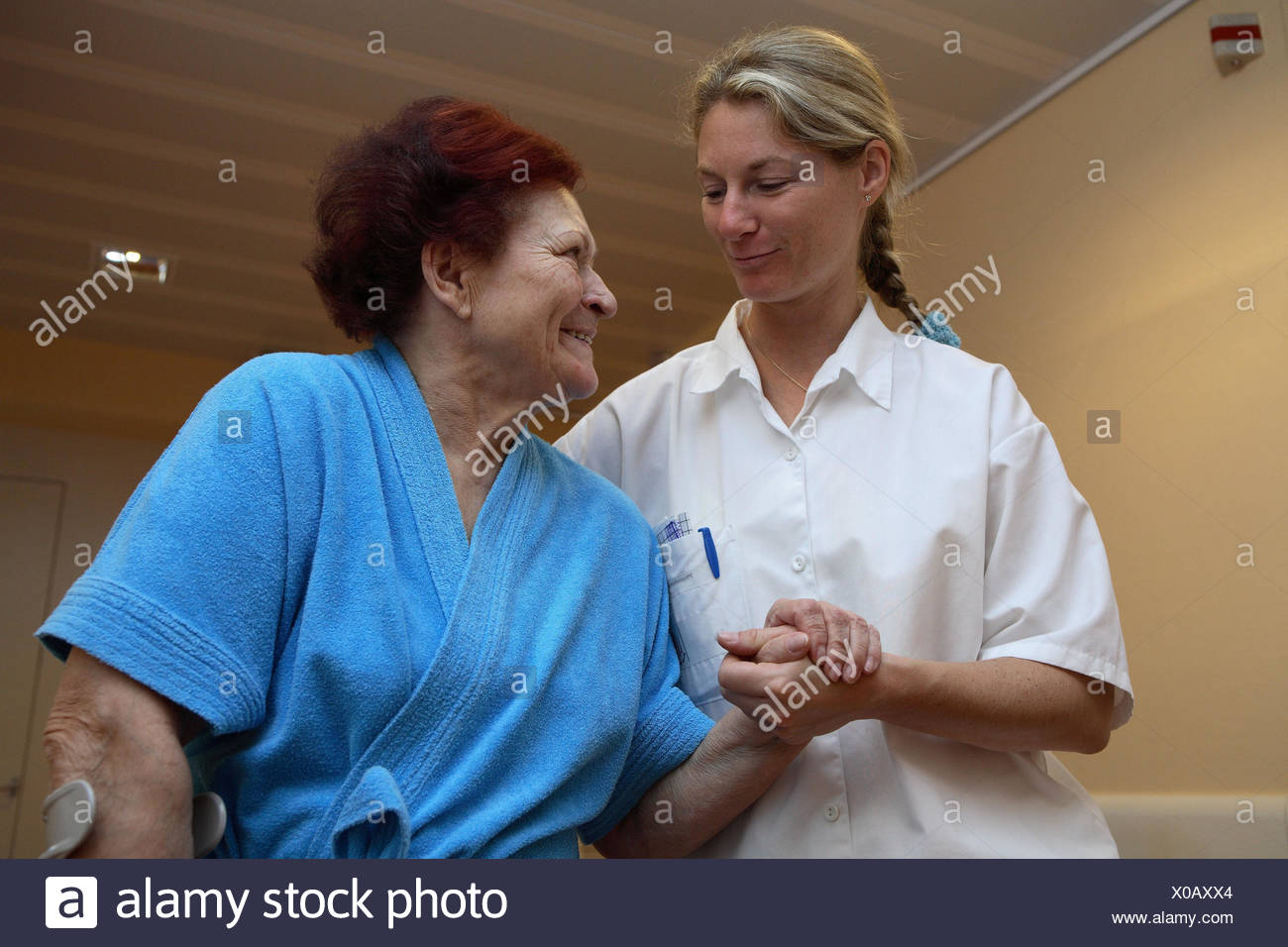 Clinic, physiotherapist, patient, senior, crutch, lead, walking practise, help, eye contact, smile, half portrait, sick person's station, ward, occupation, nursing home, nursing occupations, people, women, two, old, senior citizens, bathrobe, nursing-destitute, in need of care, Reha, nurse, nurse, nursing staff, practice, nursing force, coach, support, support, help, allowance, care, care, convalescense, healing, trust, accompaniment, gratitude, inside, - Stock Image