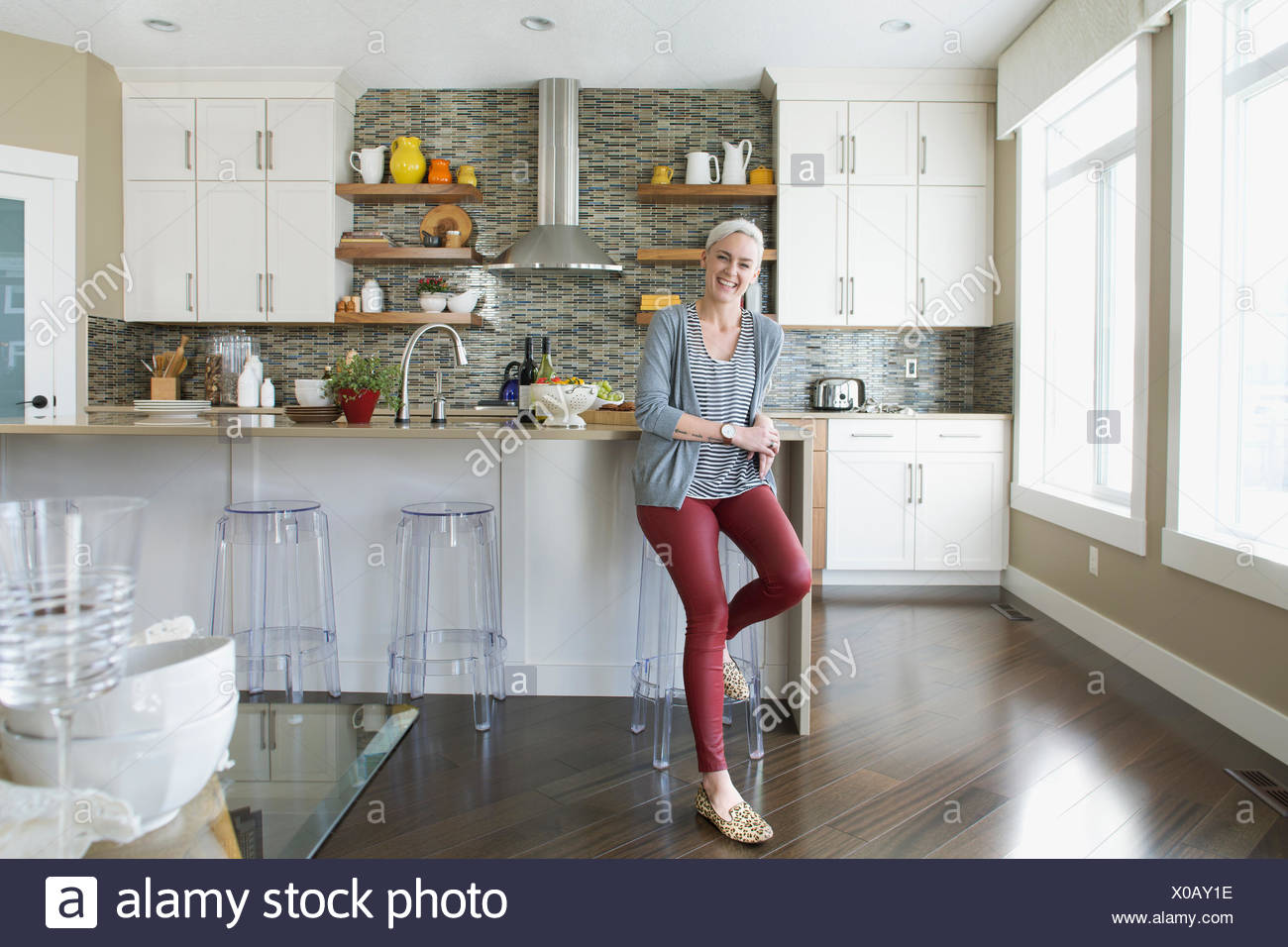 Portrait of smiling woman in kitchen - Stock Image
