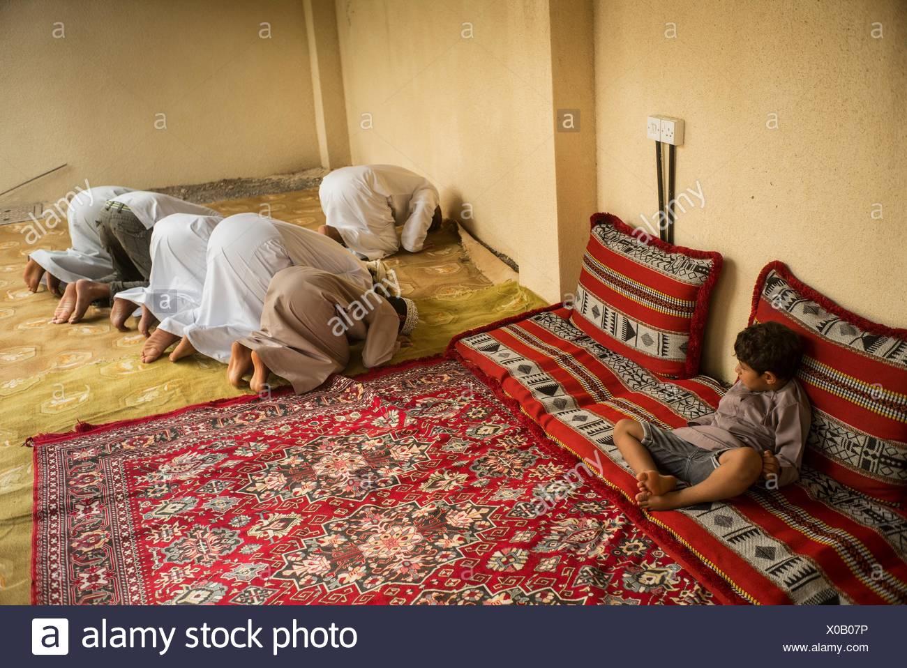 A boy watches his Muslim relatives praying. - Stock Image