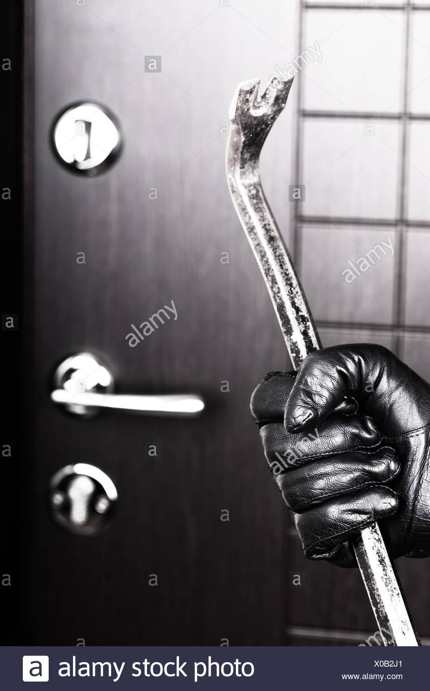 Burglar hand holding crowbar break opening door - Stock Image