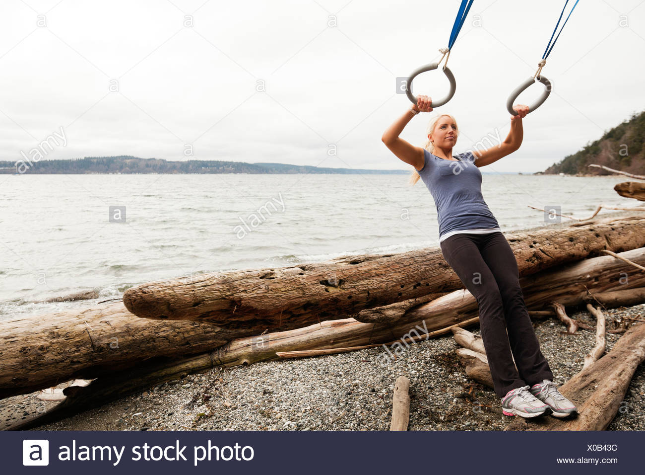 A woman performs suspension training exercises on a rustic beach. - Stock Image