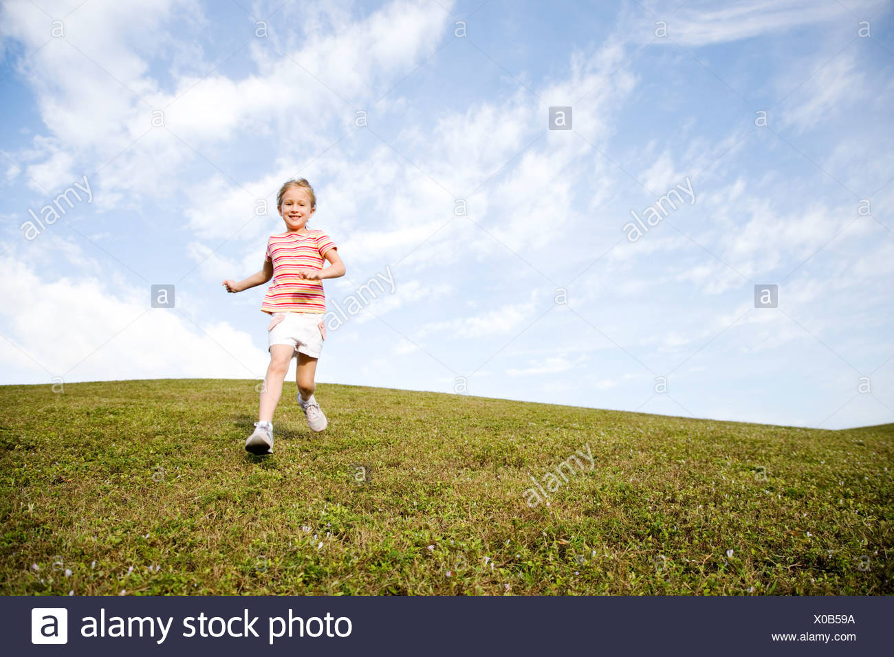 A young girl running across a hill - Stock Image