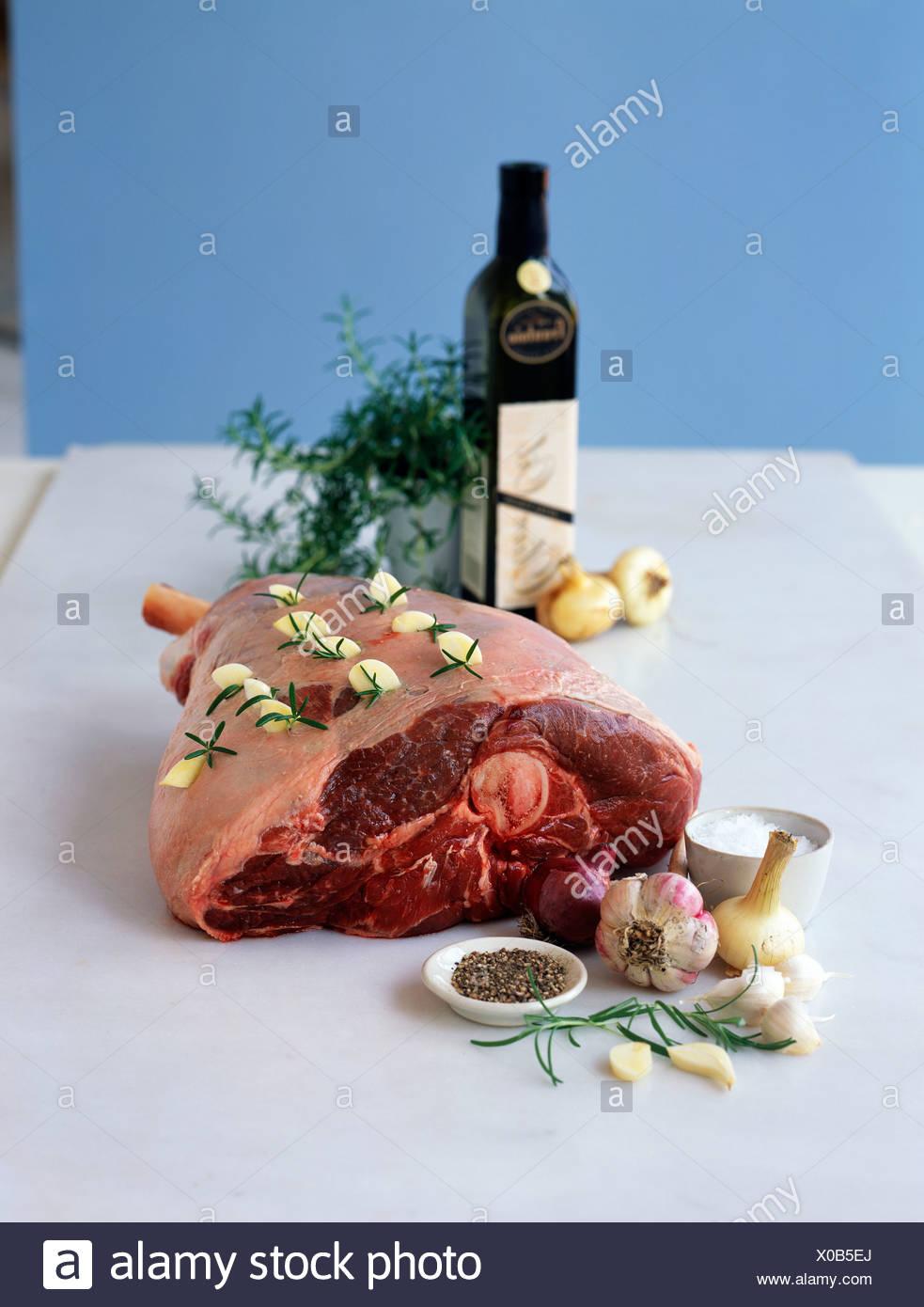 Raw leg of lamb pricked with garlic and rosemary - Stock Image