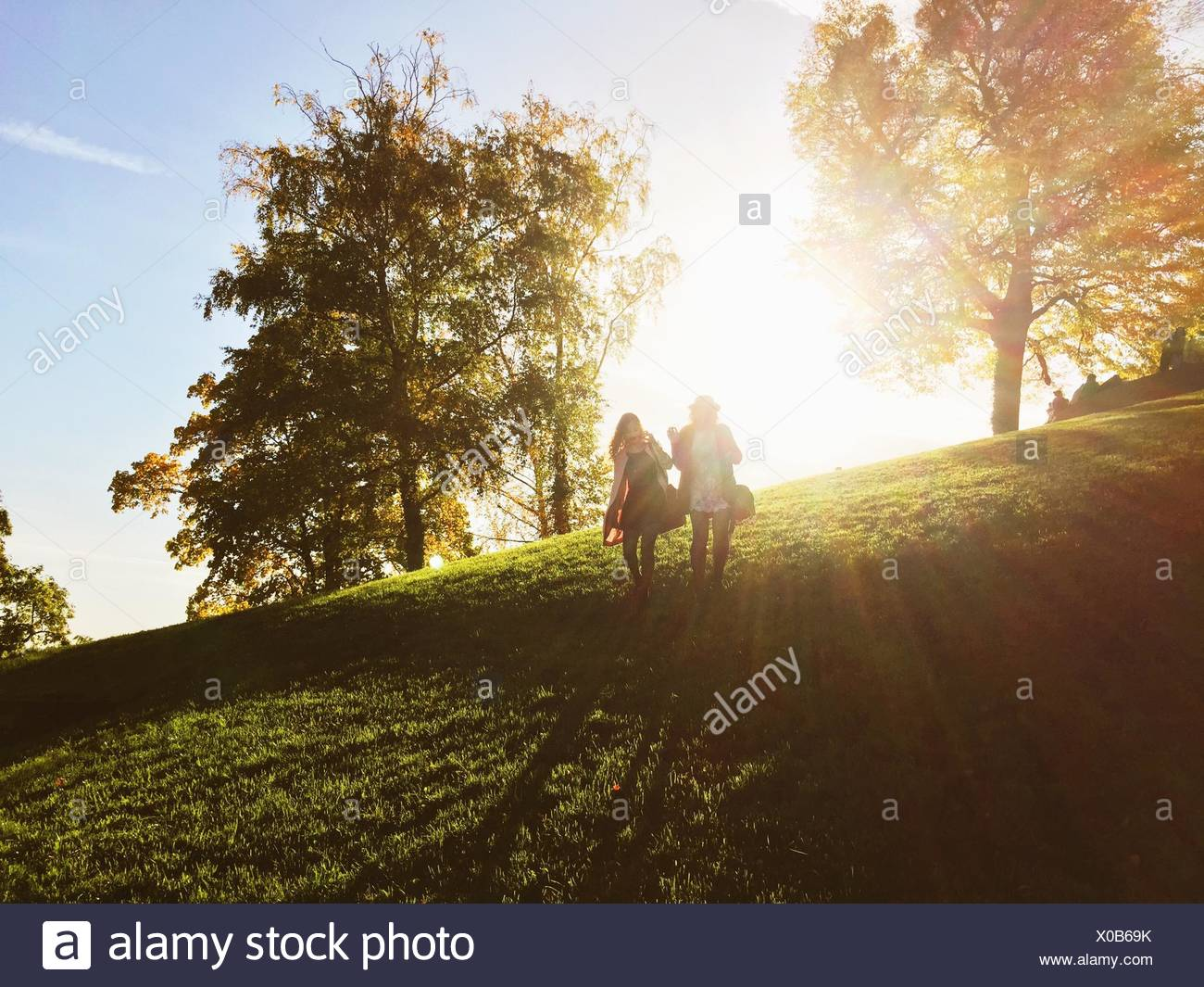 Front View Of Women Walking Down Grassy Field Against Sky - Stock Image