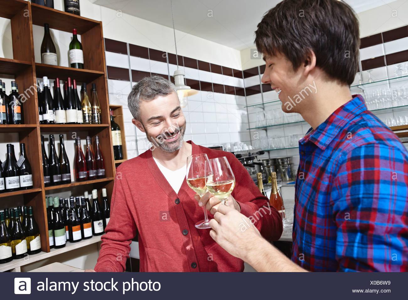 Germany, Cologne, Man having wine, smiling - Stock Image