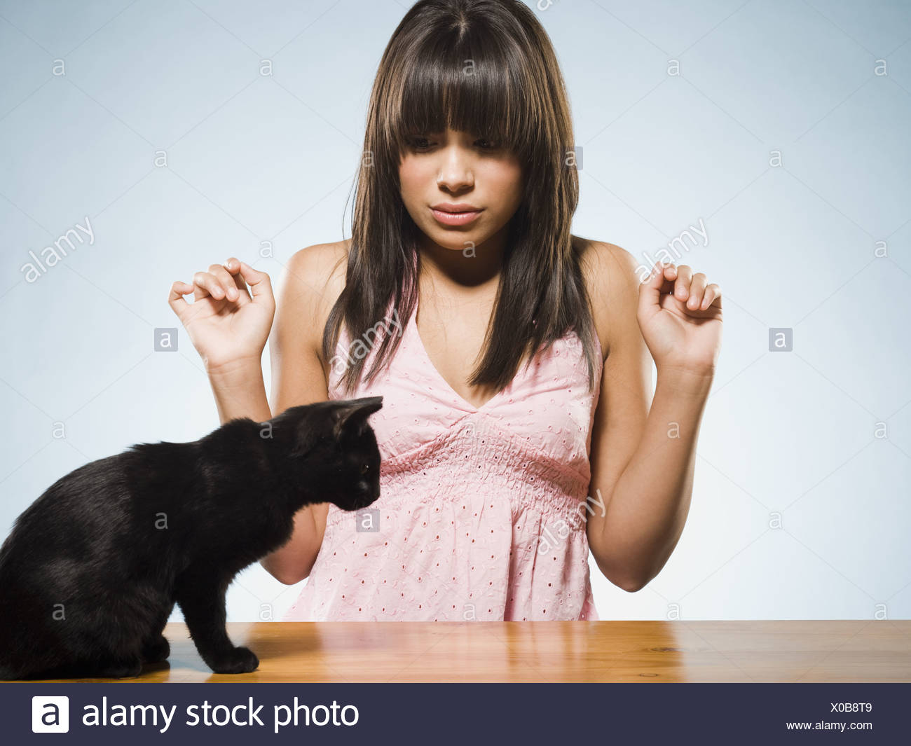Scared woman with black kitten - Stock Image