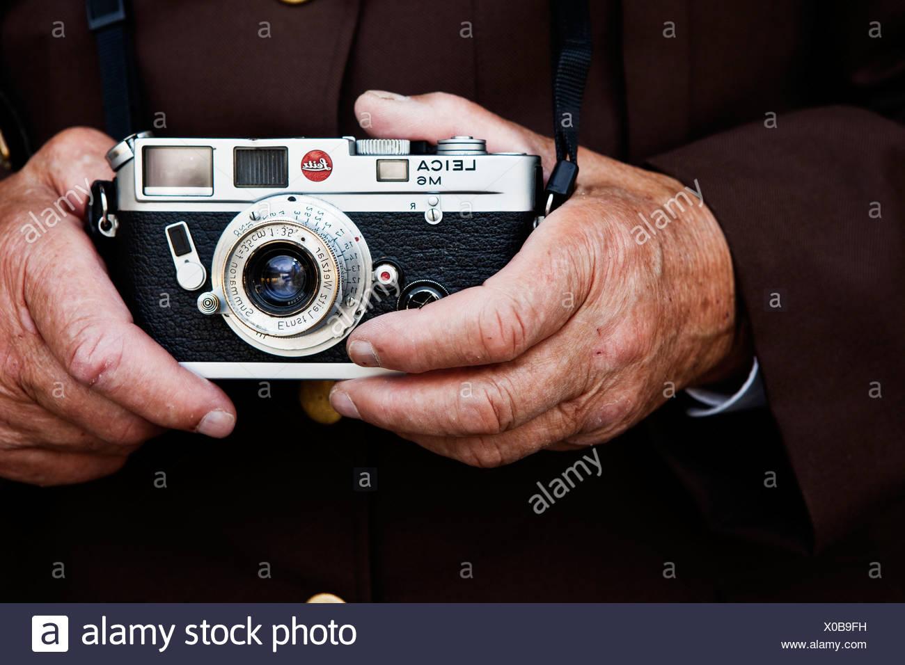 Hands of an elderly man holding a Leica rangefinder camera, North Tyrol, Austria, Europe - Stock Image