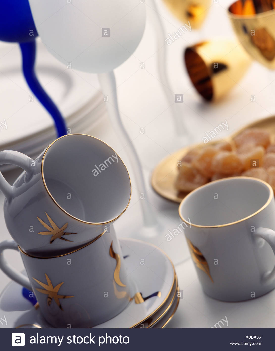 Close-up of white cups and saucers decorated with gold stamped motifs - Stock Image