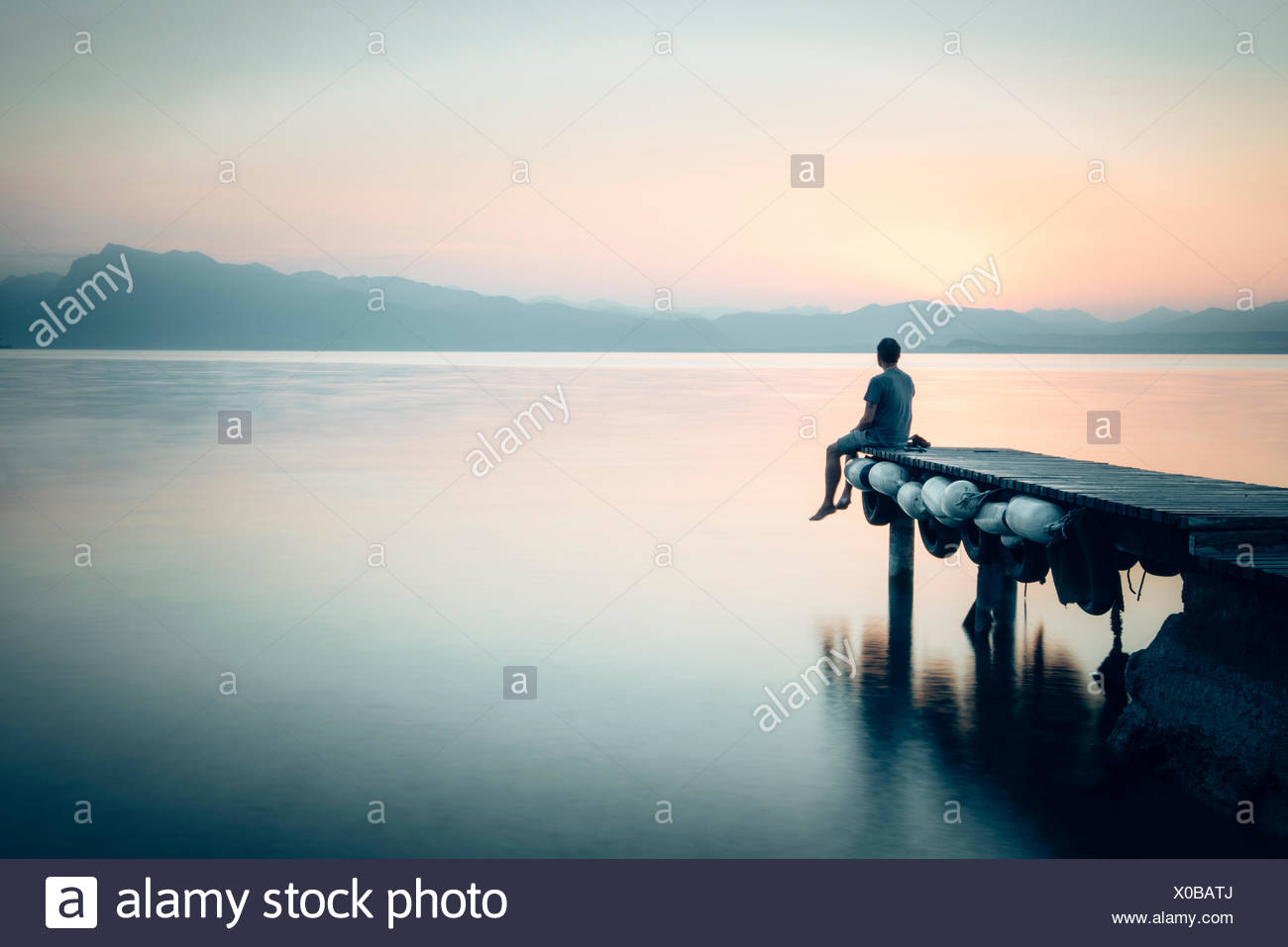 Man sitting at a jetty and looking at the lake - Stock Image