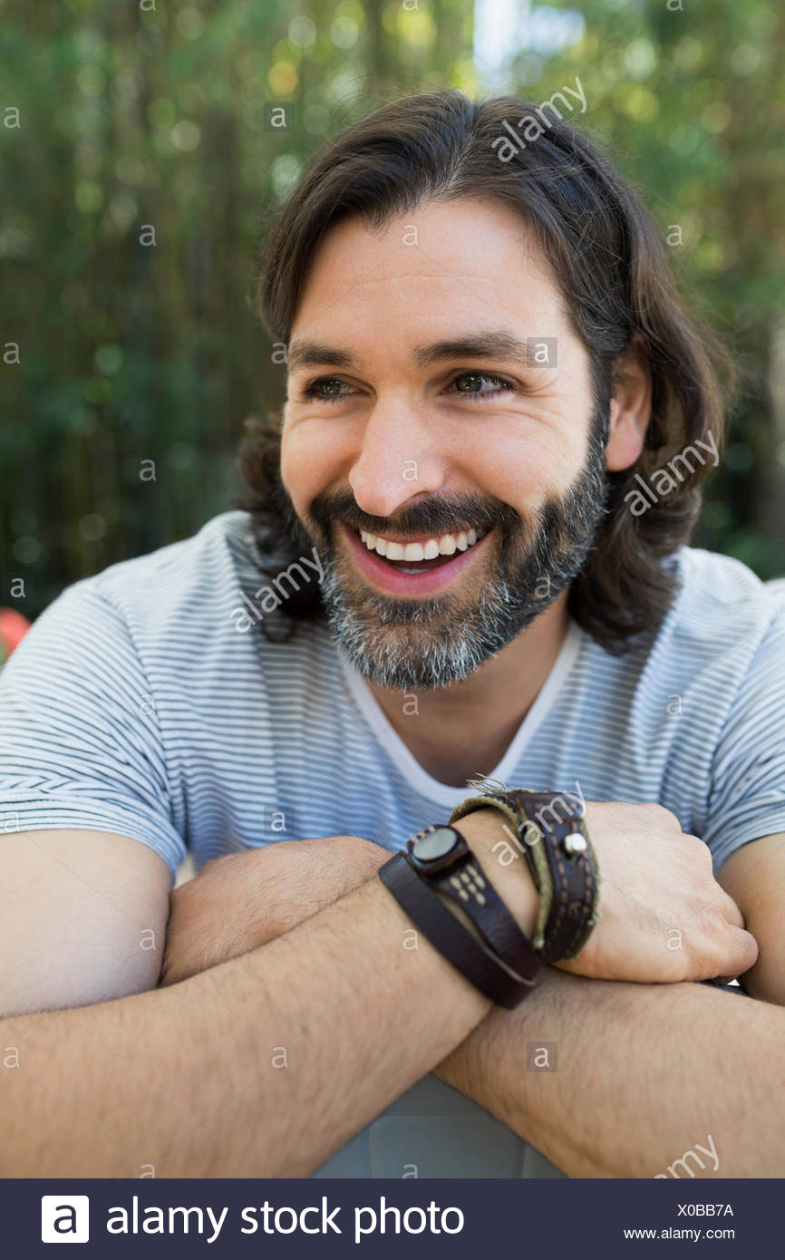 Close up portrait smiling bearded man looking away - Stock Image
