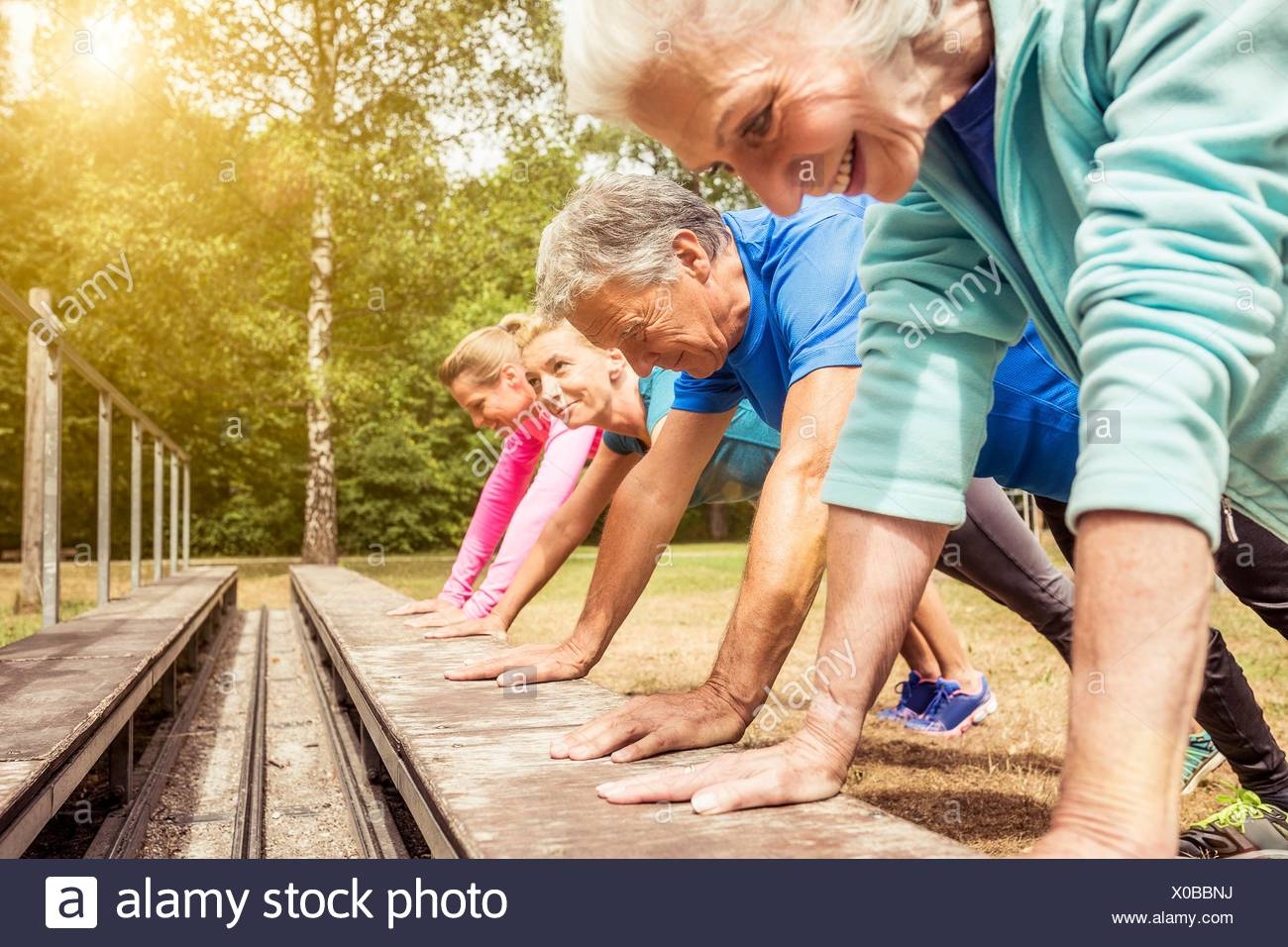 Group of adults exercising outdoors - Stock Image