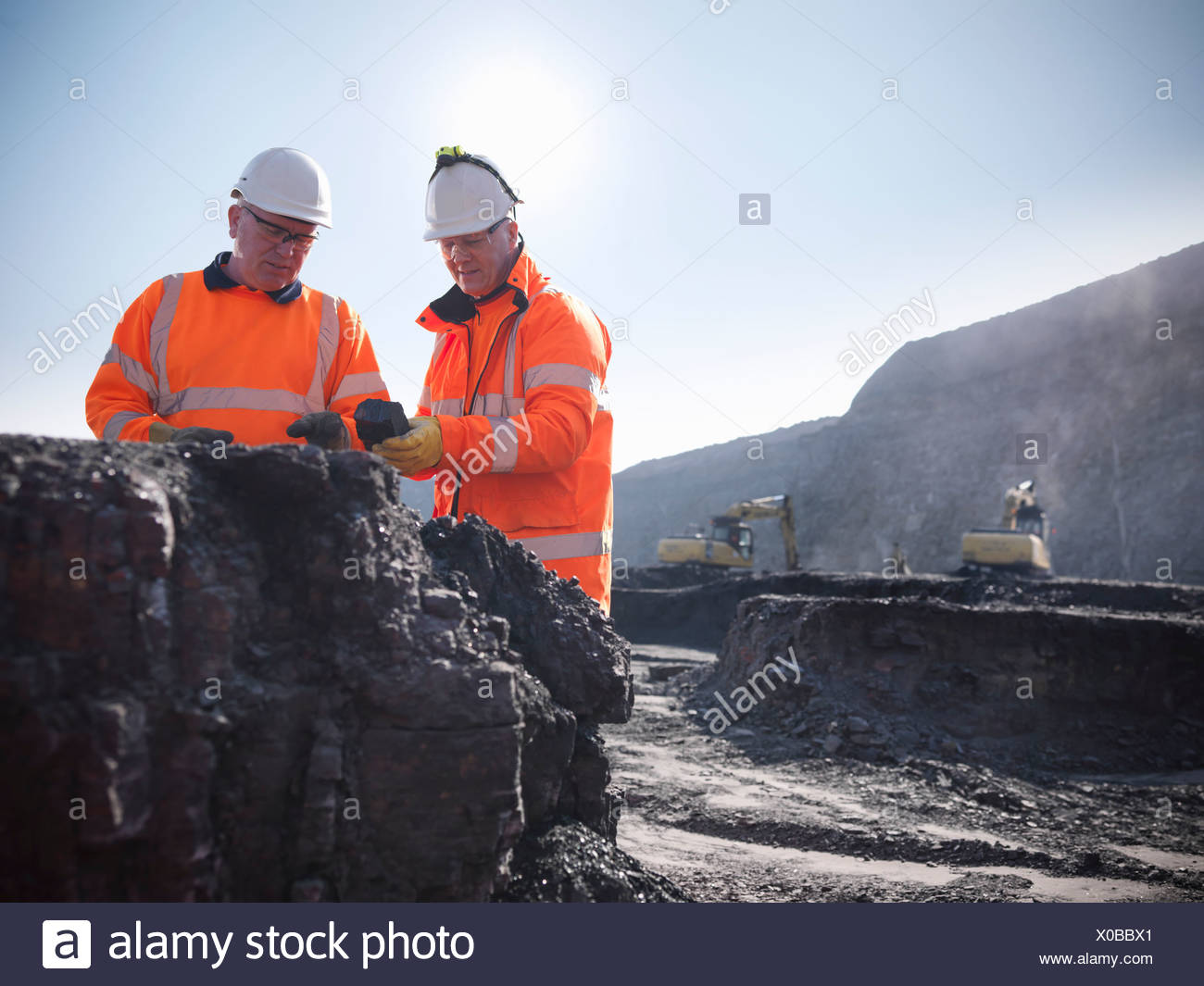 Workers inspecting coal at mine - Stock Image