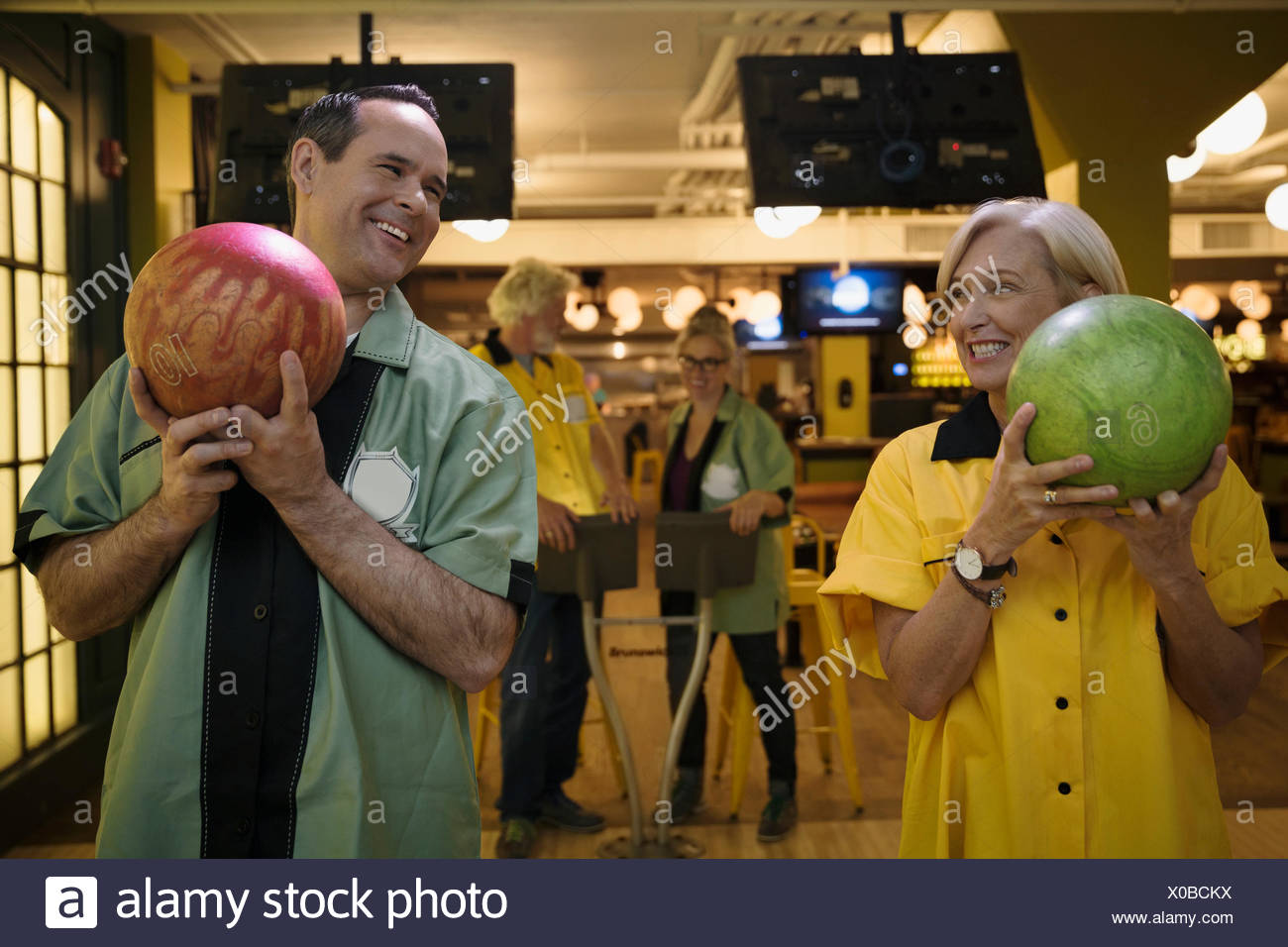 Smiling couple holding bowling balls - Stock Image