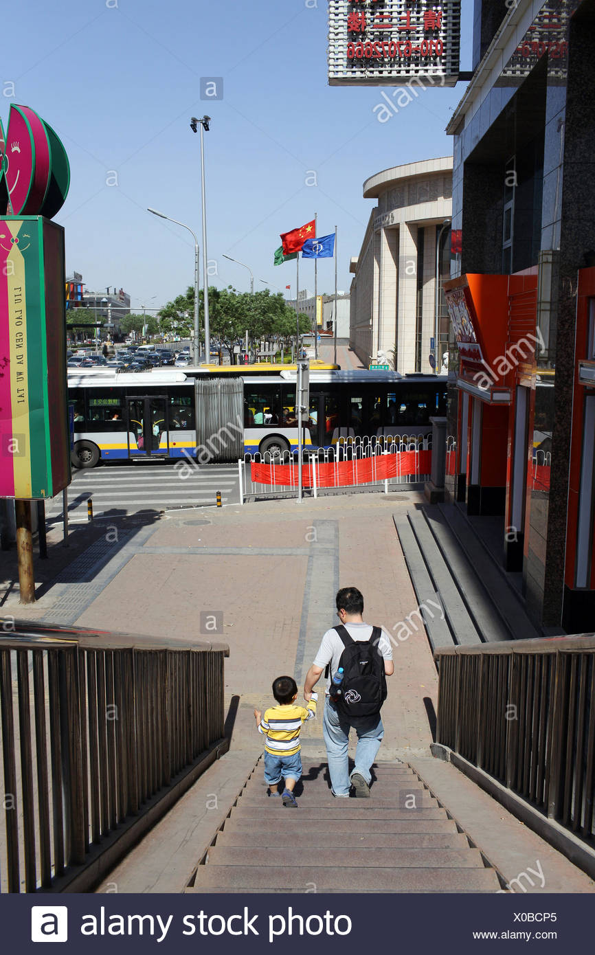 A father and son walk down stairs in the Qianmen district near Tiananmen Square. Stock Photo