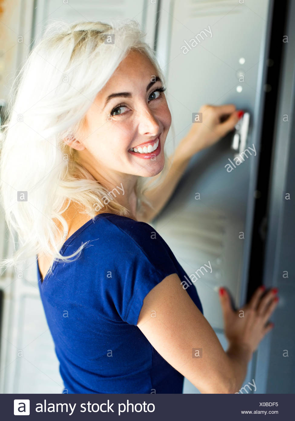 Woman opening locker - Stock Image