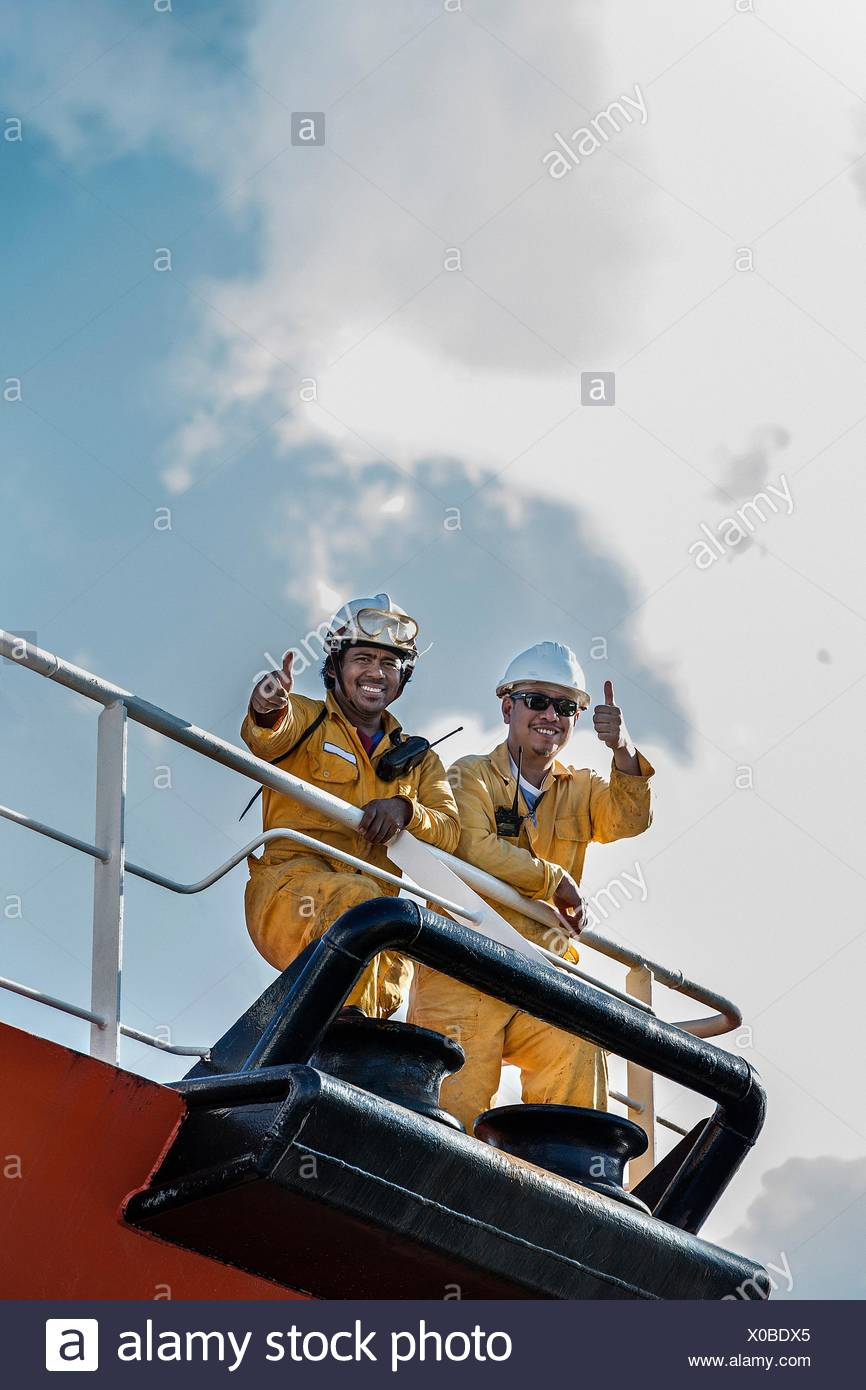 Portrait of two workers on oil tanker giving thumbs up - Stock Image