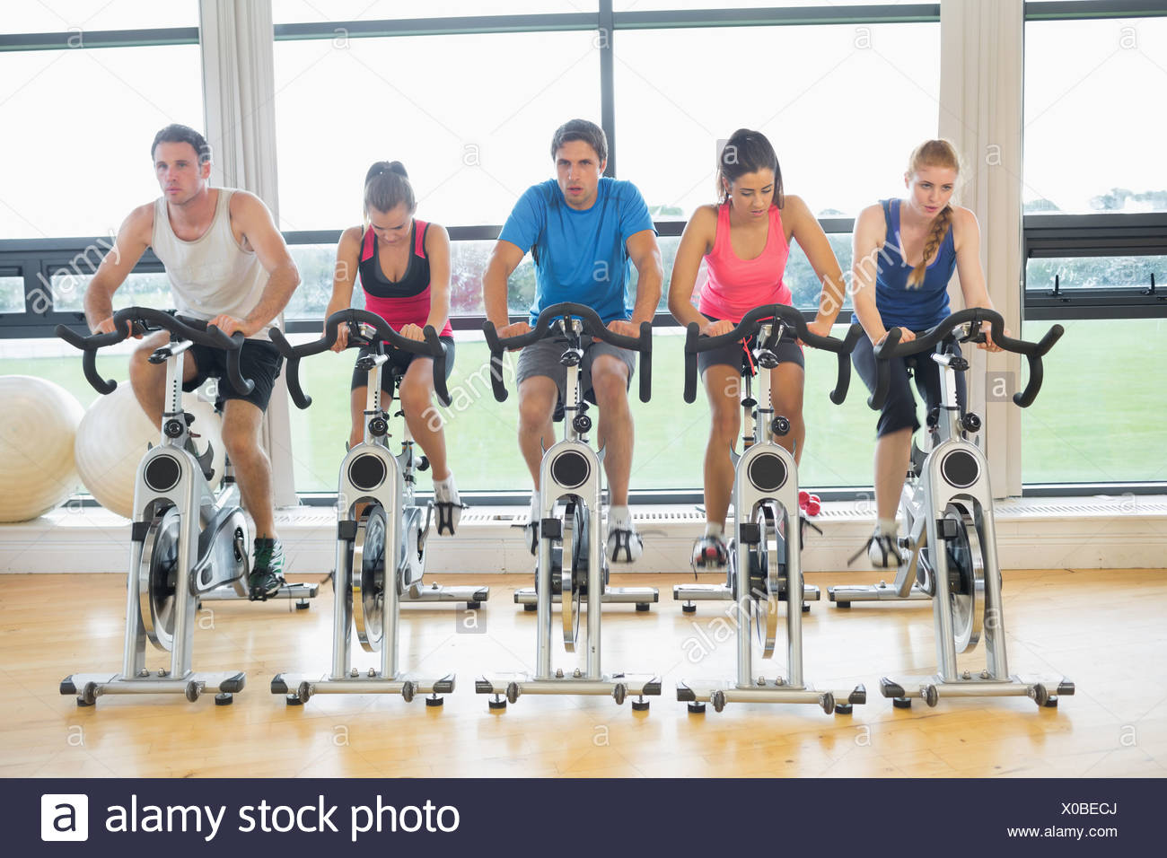 Determined people working out at spinning class in gym Stock Photo