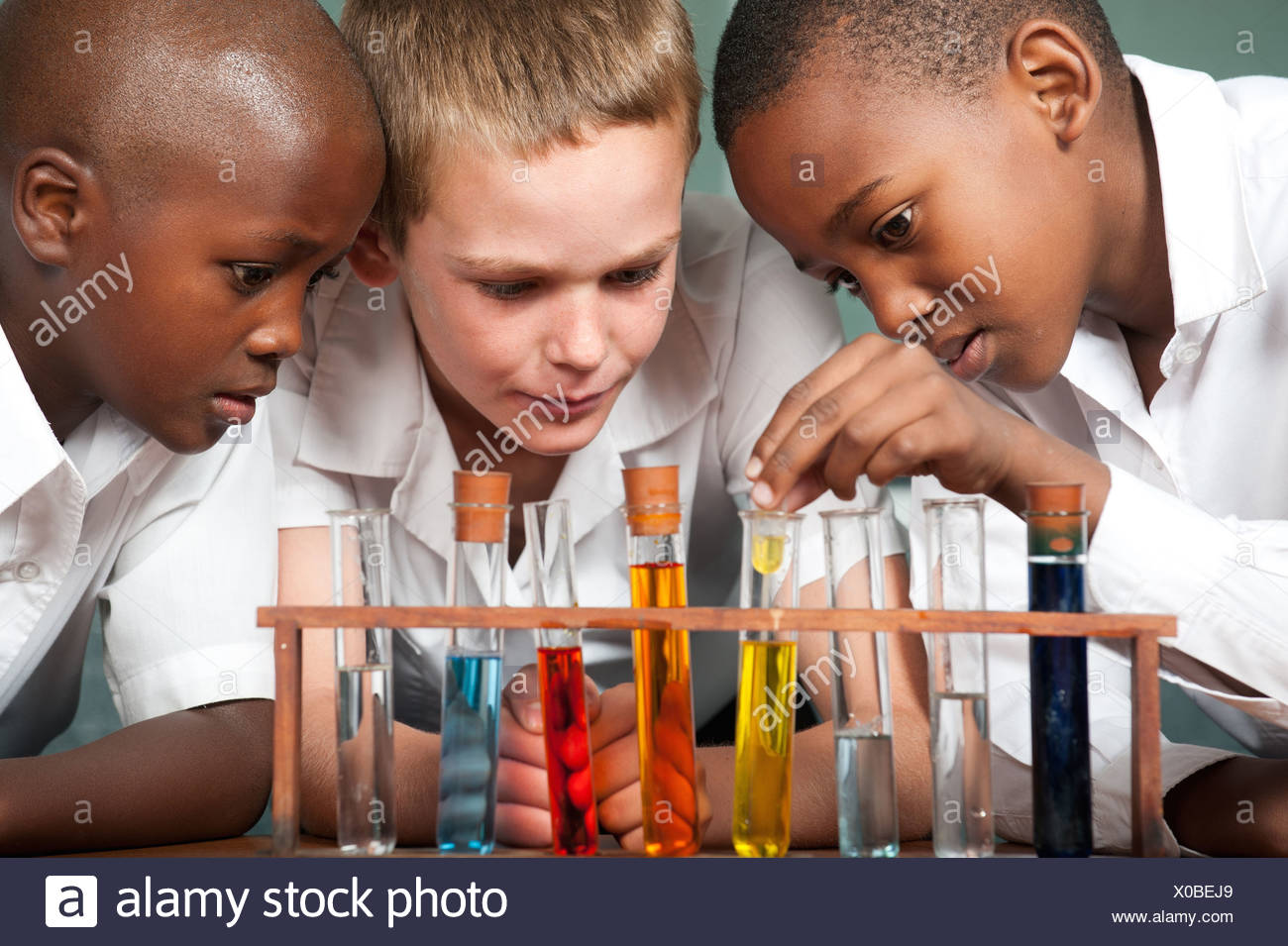 Three boys looking at test tubes in classroom, Johannesburg, Gauteng Province, South Africa - Stock Image