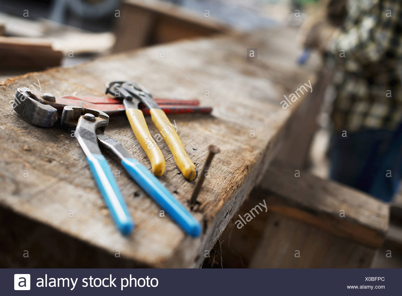 A reclaimed lumber workshop A person at a workbench and tools grippers and pliers lined up on a plank of wood - Stock Image