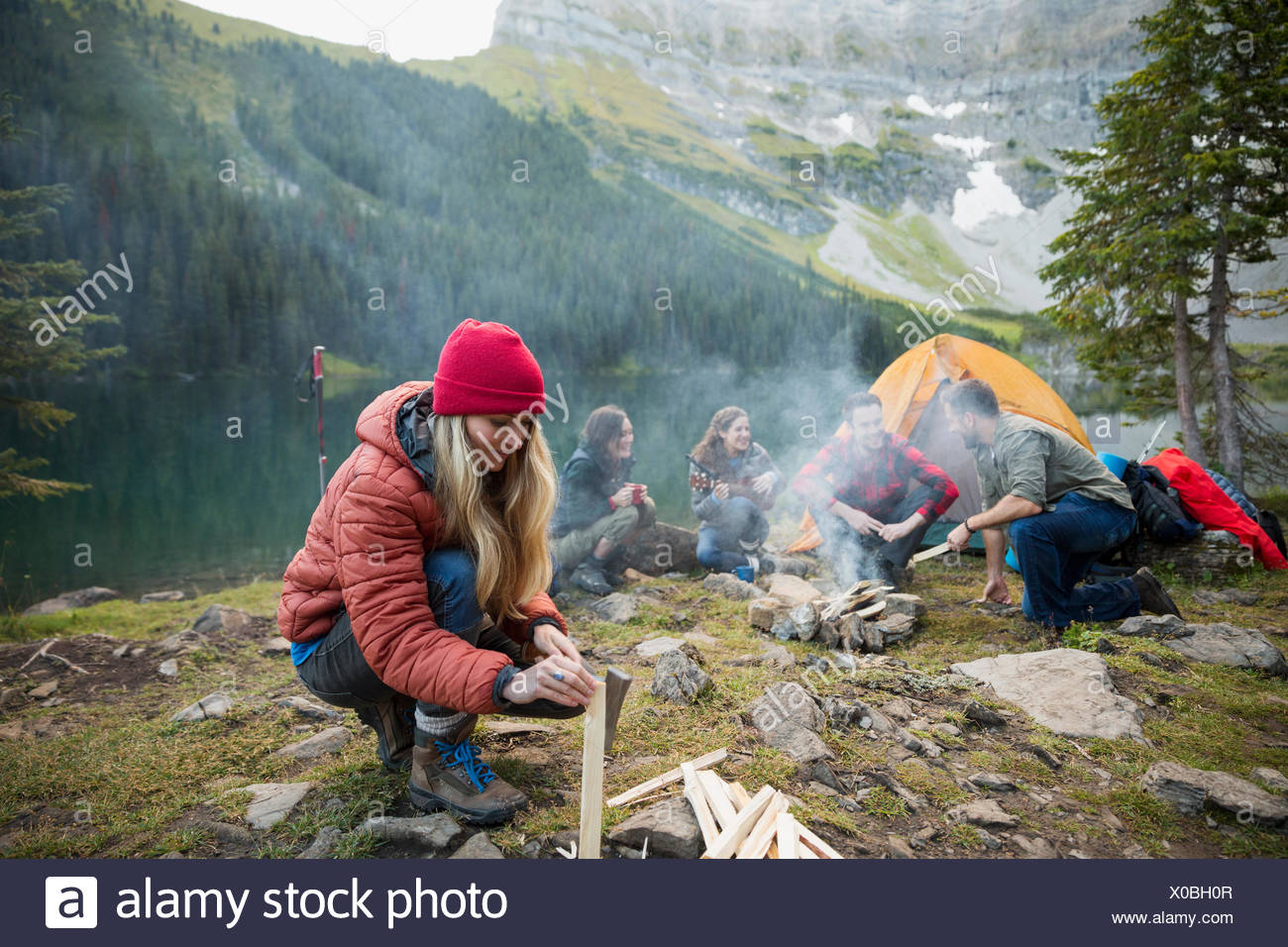 Woman splitting firewood at remote lakeside campsite - Stock Image