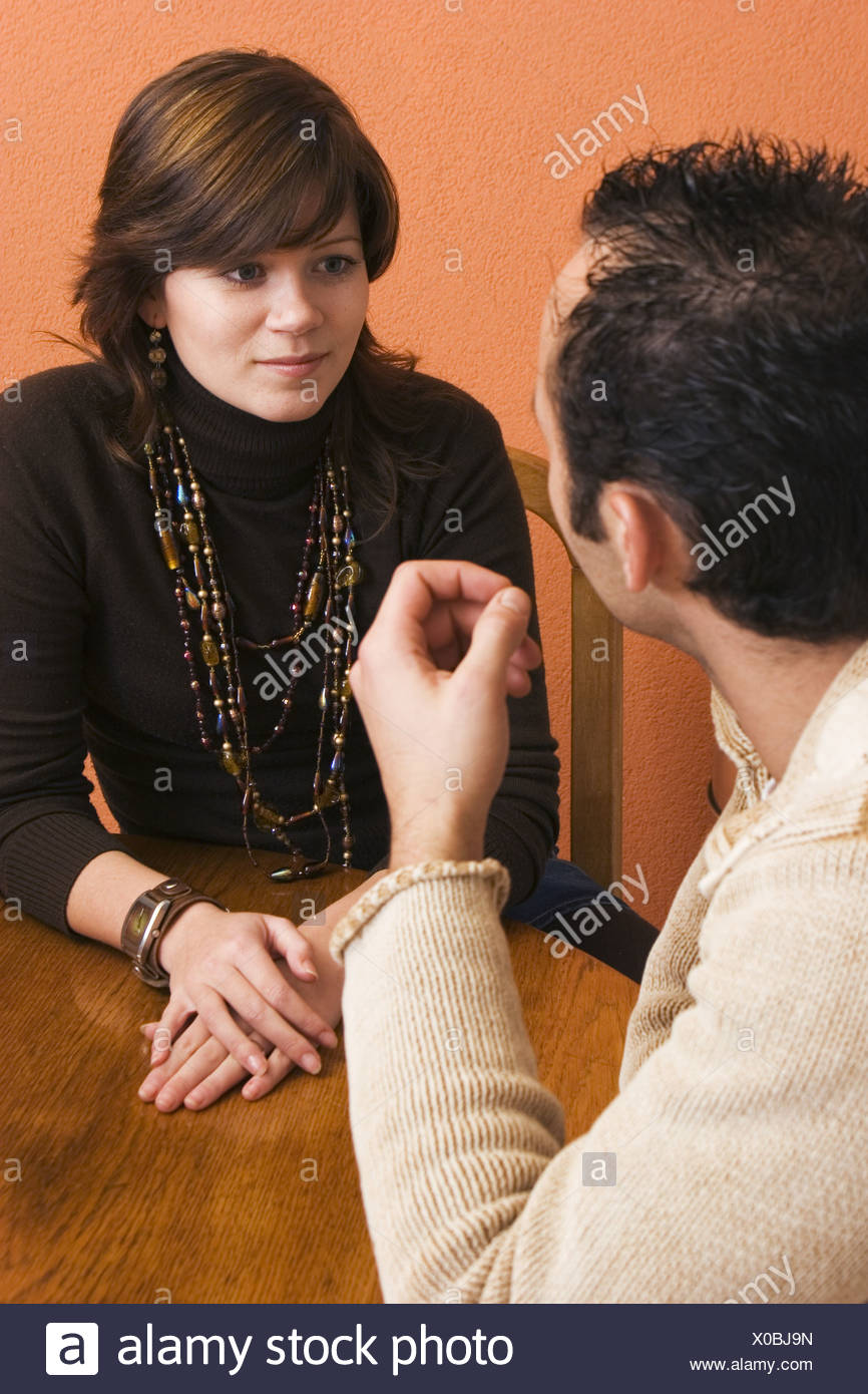 Young couple serious conversation at table - Stock Image