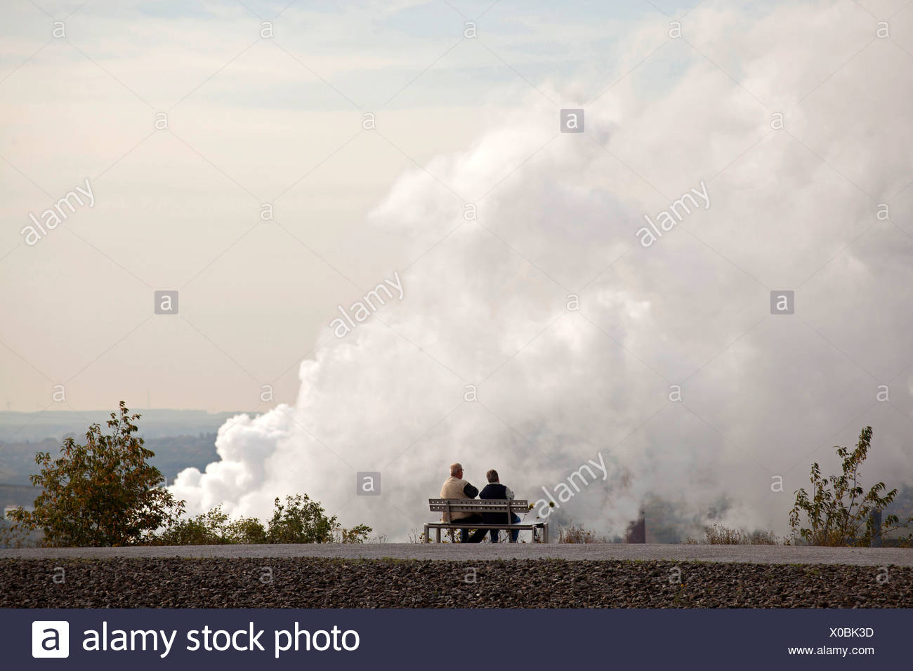 Couple on a bench in front of air pollution from a power plant in Bottrop, Ruhr Area, North Rhine-Westphalia - Stock Image