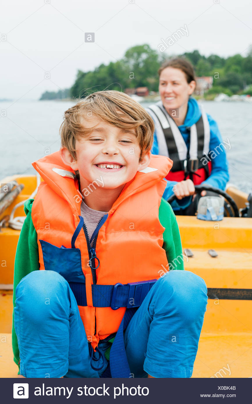 Sweden, Uppland, Runmaro, Barrskar, Portrait of boy (6-7) on motorboat, mother in background - Stock Image