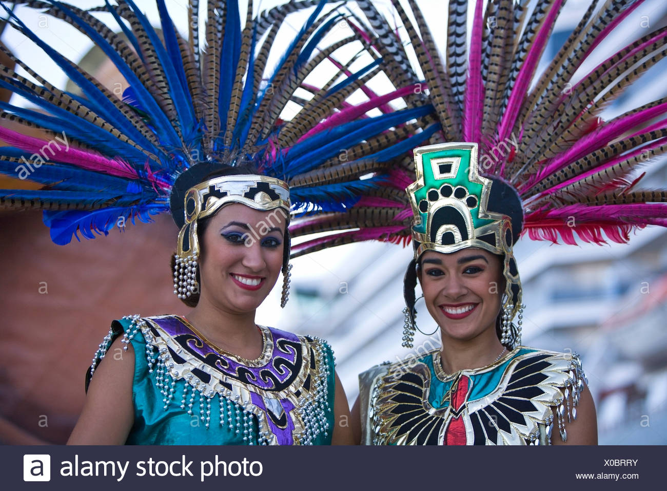 Two women in Aztec outfits, wearing feather headdress with Pheasant feathers, Cruise Ship Terminal; Mazatlan, Sinaloa, Mexico - Stock Image