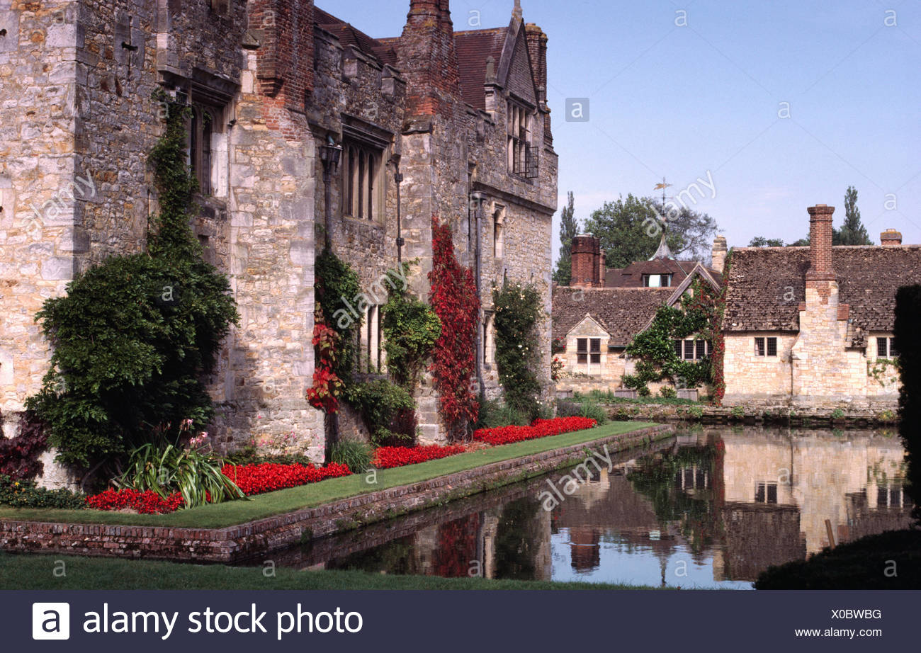 Exterior of a large, fortified country house with a moat and bright red salvias in a neat border - Stock Image