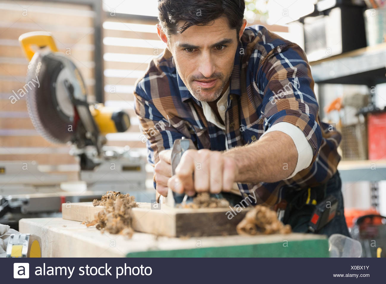 Carpenter smoothing wood with plane in workshop - Stock Image