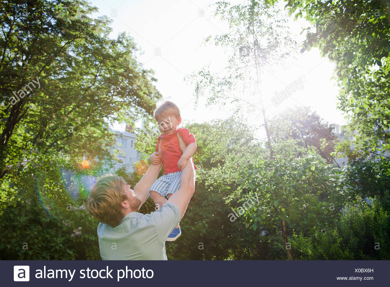 Father holding up toddler son in park - Stock Image