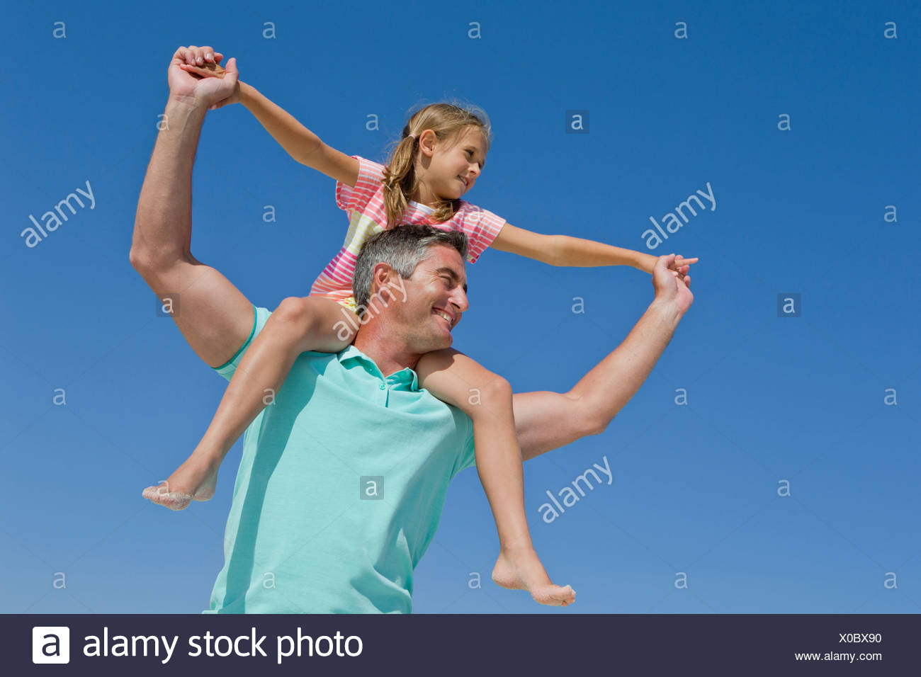 Father carrying daughter on shoulders against blue sky - Stock Image