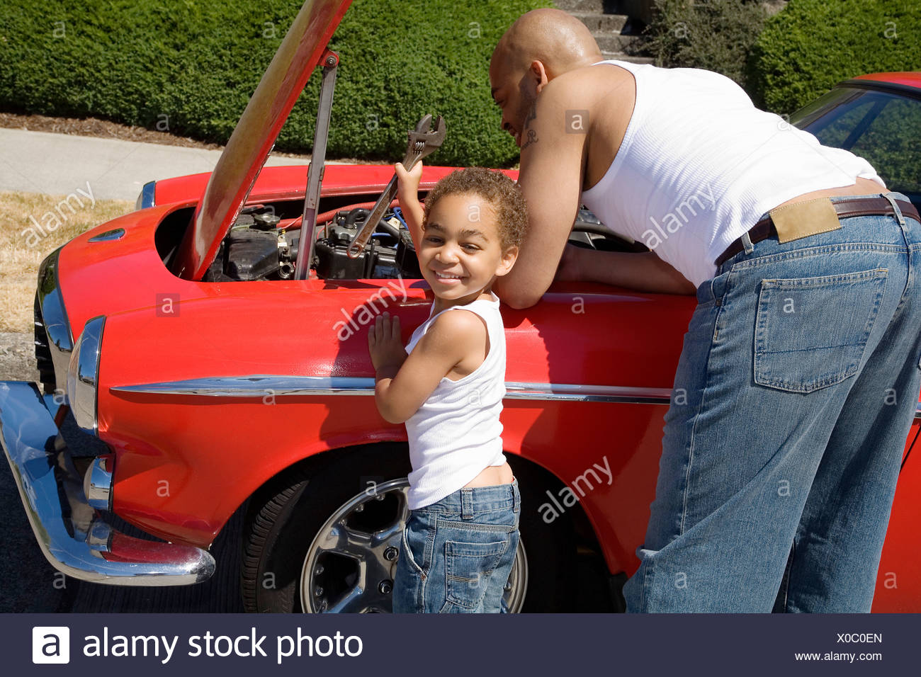 Young boy helping his father work on car - Stock Image