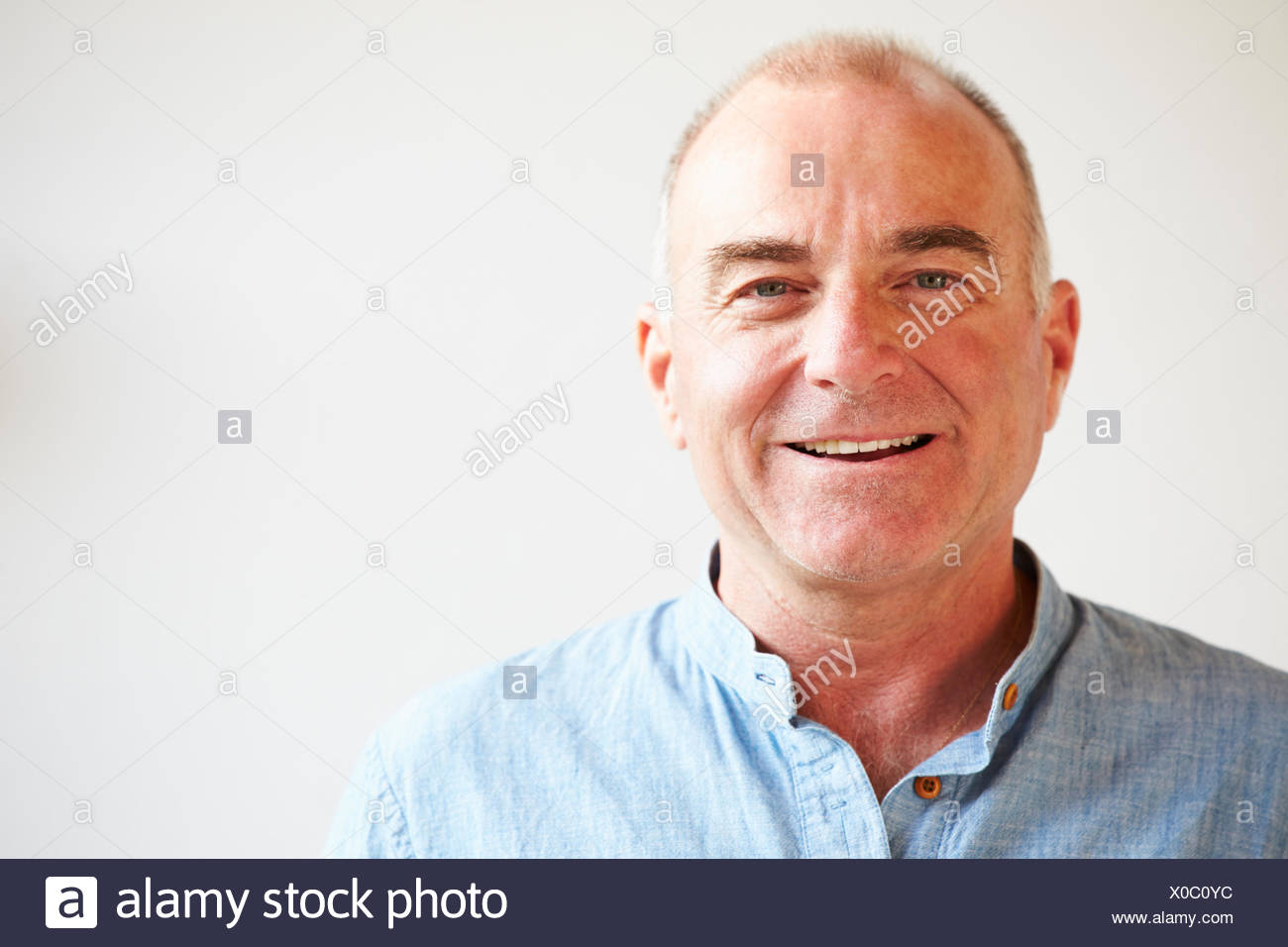 Portrait Of Middle Aged Man Standing By Wall - Stock Image