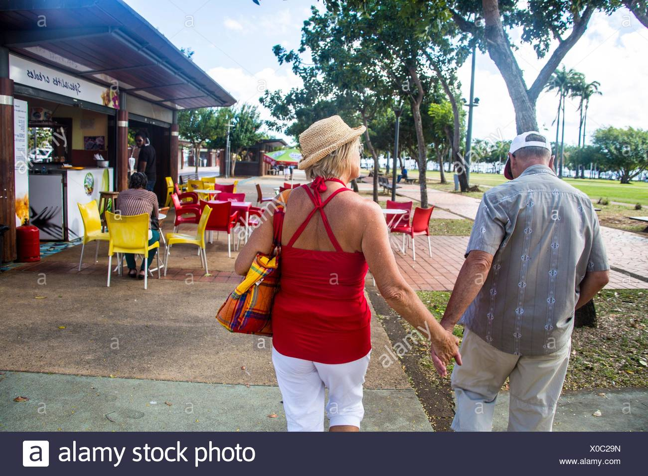 Older mature retired caucasian couple holding hands in the streets of Fort de France on a vacation. He wears a baseball hat and she a straw hat. - Stock Image