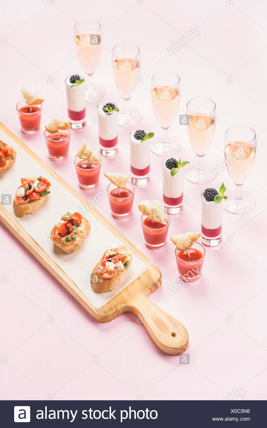Catering, banquet or party food concept. Various snacks, brushetta sandwiches, gazpacho shots, desserts with berries in glasses on corporate event, ch - Stock Image