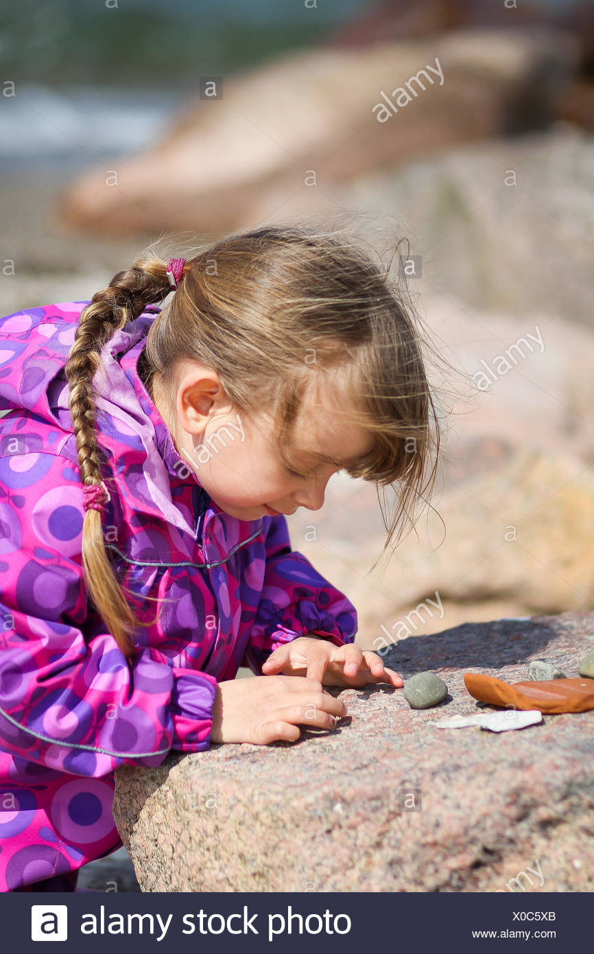 A young girl with long hair examining her collection of pebble. - Stock Image
