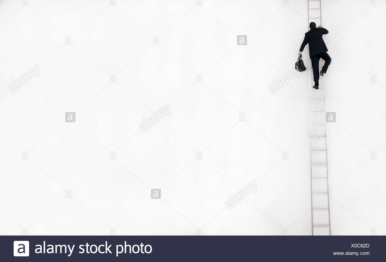 Man in business suit climbs a tall ladder, San Diego, California. - Stock Image