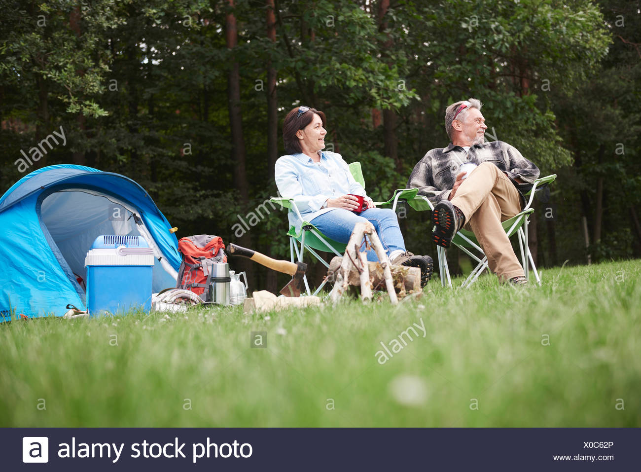 Mature couple sitting in camping chairs beside tent, low angle view - Stock Image