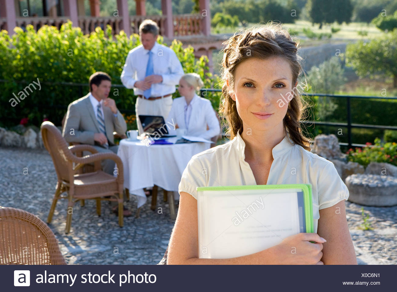 Confident businesswoman holding paperwork at café with coworkers in background - Stock Image