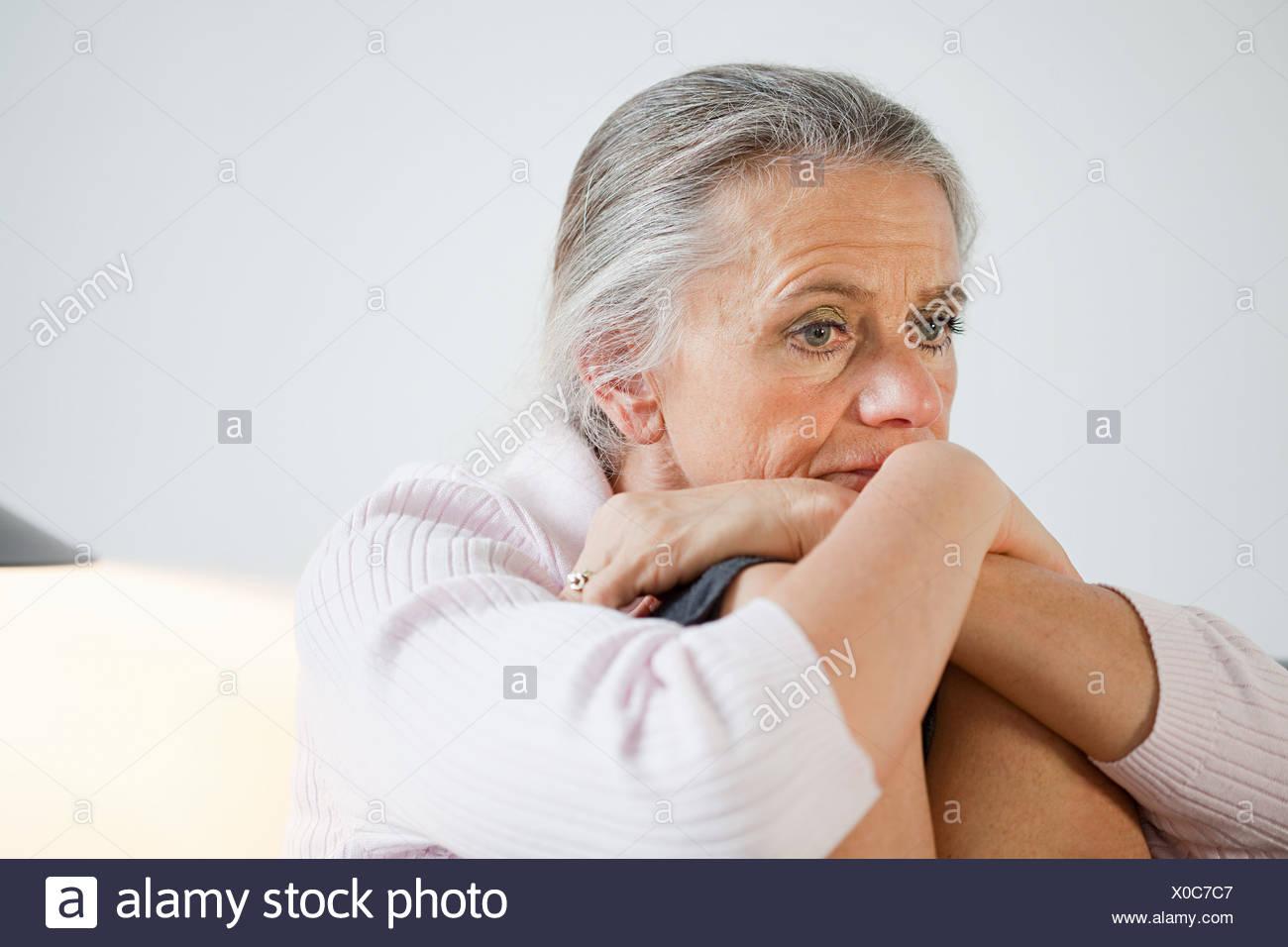 Mature woman looking anxious - Stock Image